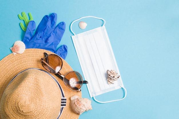 Dromen van vakantieconcept, strohoed, rubberen handschoenen, zonnebril, schelpen en een beschermend gezichtsmasker op een blauw oppervlak
