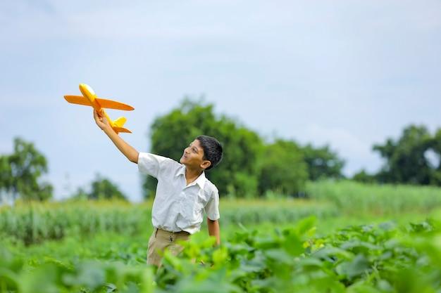 Dromen van vluchten! indiase kind spelen met speelgoed vliegtuig op groen veld
