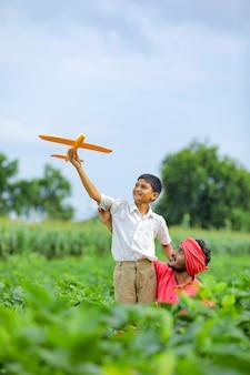 Dromen van vluchten! indisch kind speelt met speelgoed vliegtuig met zijn vader op cyclus