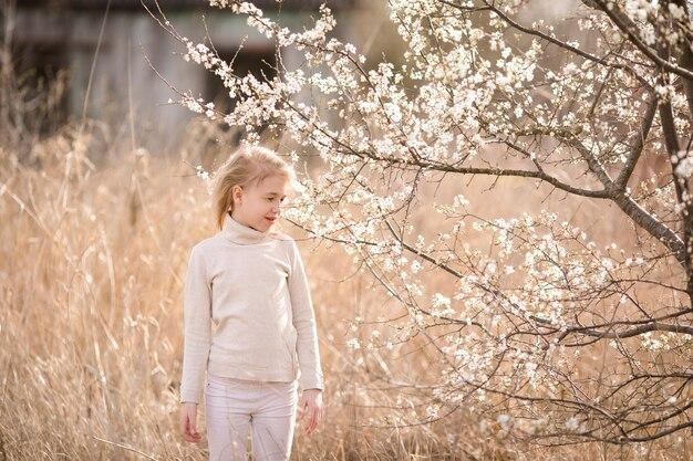 Dromend blondemeisje in de witte kleren in de bloesemtuin dichtbij de witte bloemen van sakura.