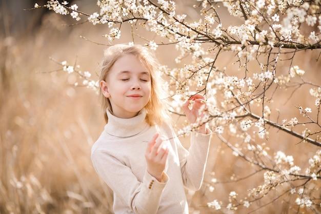 Dromend blondemeisje met gesloten ogen in de bloesemtuin dichtbij de witte bloemen van sakura. lente kersenboom en warme zonnige thema