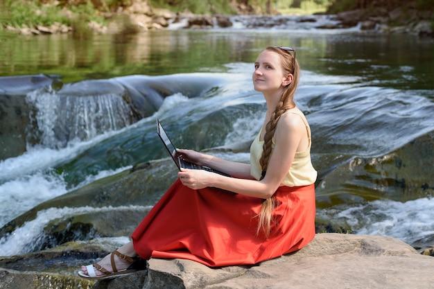 Dromend mooi langharig meisje in een rode rok zit met een laptop op een steen tegen de achtergrond van een waterval van een bergrivier. freelance-concept. werk in de natuur.