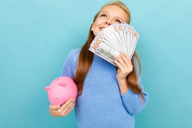 Dromend vrolijk meisjesschoolmeisje tegen een blauwe muur met een spaarvarken en een ventilator van geld