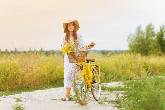 Dromende jonge dame houdt haar fiets vast terwijl ze ermee loopt op een veld met gele bloemen
