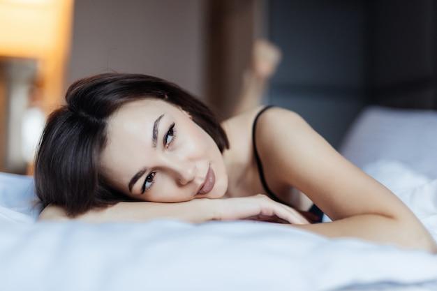 Dromende sexy jonge vrouw in bed in de vroege ochtend