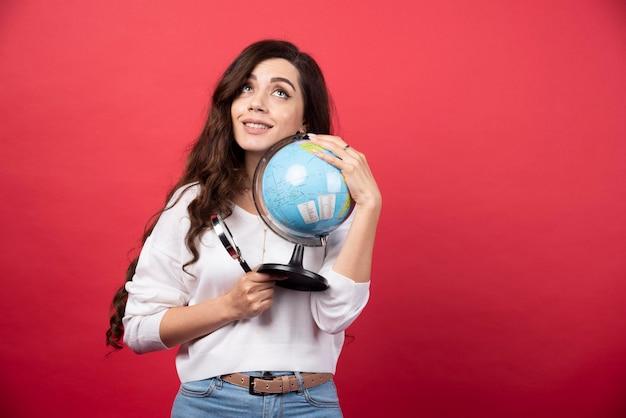 Dromende vrouw die globe en vergrootglas stevig vasthoudt. hoge kwaliteit foto