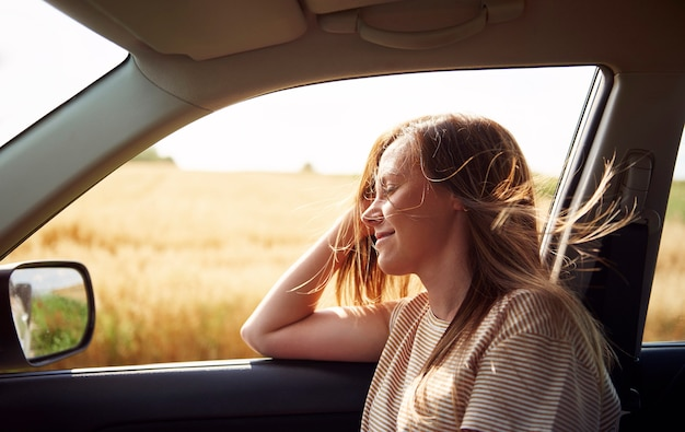 Dromende vrouw die met de auto reist