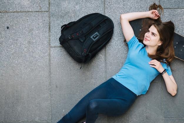 Dromerende tiener liggend op skateboard