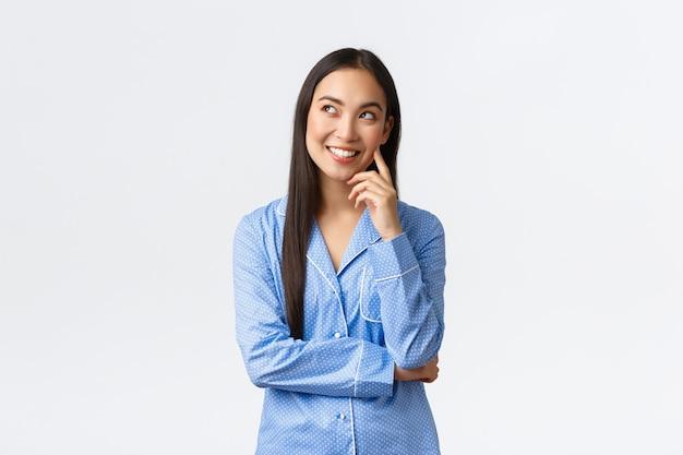Dromerig bedachtzaam aziatisch meisje in blauwe pyjama met interessant idee, kijkend in de linkerbovenhoek naar commentaarbel, glimlachend blij als denkend, dagdromen voordat ze naar bed gaan, witte achtergrond.