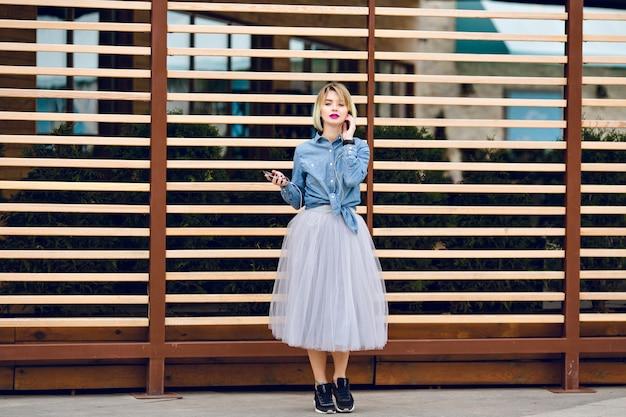 Dromerig blond meisje met felroze lippen staan en luisteren naar muziek op een smartphone met gestreepte houten balk achter
