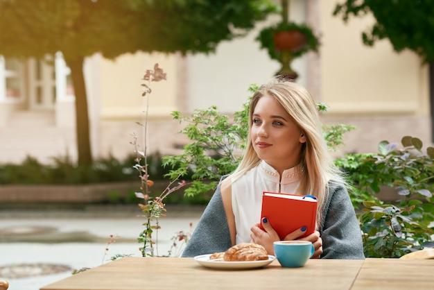 Dromerig blondemeisje die rode boekzitting in openlucht houden.