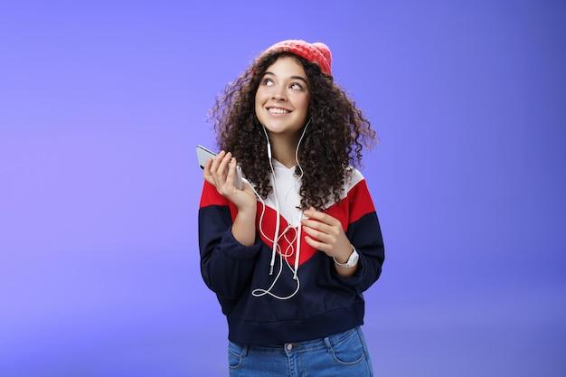 Dromerig charmant en gelukkig aardig meisje dat mooie herinneringen oproept als nostalgisch luisterend lied in oortelefoons...