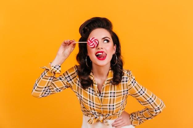 Dromerig donkerbruin meisje dat lolly eet. studio shot van pinup jonge vrouw met snoep staande op gele achtergrond.