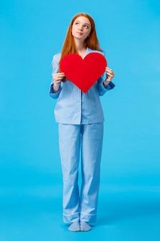 Dromerig en creatief, roodharig kaukasisch meisje dat denkt hoe haar toekomstige liefde eruit ziet, opkijkend met behulp van verbeelding, nadenkend met geïntrigeerde uitdrukking, hart valentines kaart vasthouden, blauwe muur
