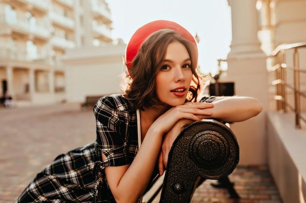 Dromerig frans meisje poseren op de bank. openluchtportret van debonair krullend vrouwelijk modelzitting op stad.