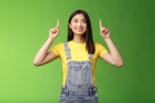 Dromerig, hoopvol, schattig aziatisch meisje kijkt geamuseerd omhoog, lacht verrukt, overweeg interessant object, geniet van sterrenkijken, grijnzen tevreden, staren naar toppromo, staan op groene achtergrond.