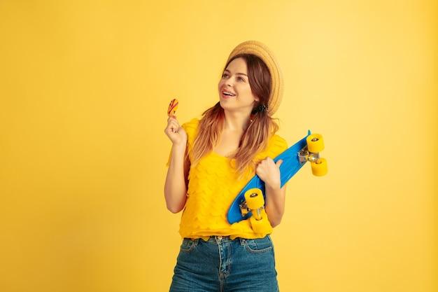 Dromerig, houdt skate vast. het portret van de kaukasische vrouw op gele studioachtergrond.