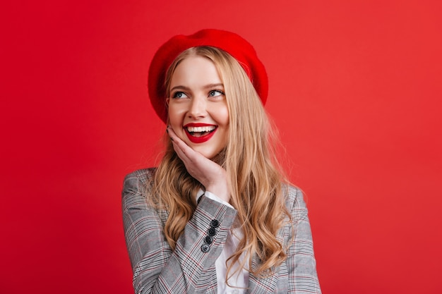 Dromerig kaukasisch meisje dat met blond haar met glimlach omhoog kijkt. positieve franse vrouw in baret geïsoleerd op rode muur.