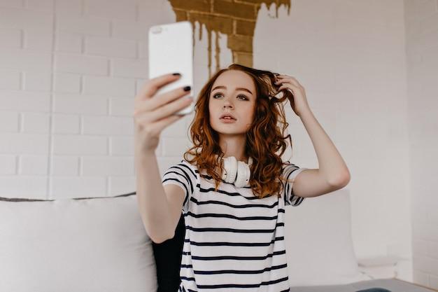 Dromerig kaukasisch meisje selfie maken. elegante gember vrouw met smartphone en het nemen van foto van zichzelf.
