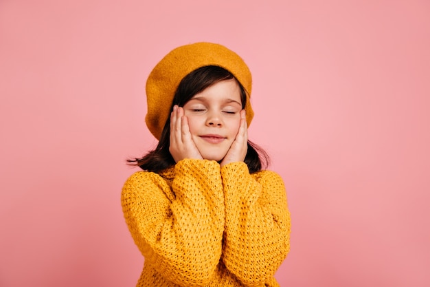 Dromerig kind poseren met gesloten ogen. zorgeloze jongen geïsoleerd op roze muur.