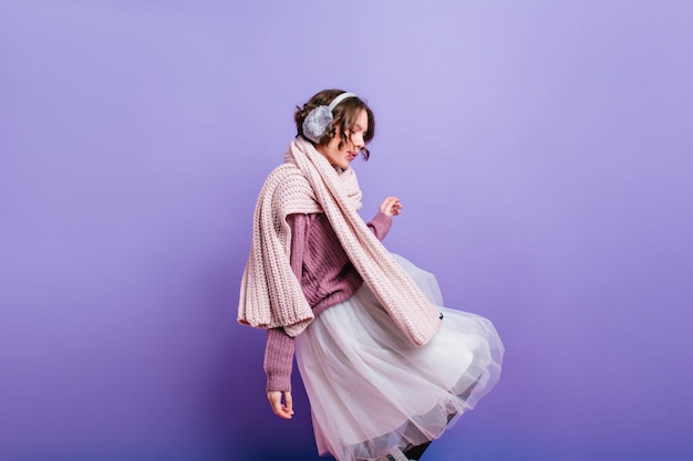 Dromerig kortharig meisje in weelderige rok en bontkoptelefoon poseren met plezier. blanke vrouw draagt gebreide sjaal wegkijken.