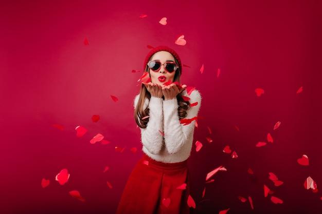 Dromerig meisje dat met lichte make-up luchtkus verzendt op bordeauxrode ruimte