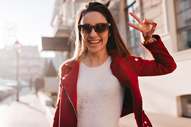 Dromerig meisje draagt een wit overhemd en een rood jasje dat geluk op straat uitdrukt