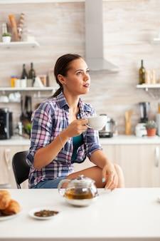 Dromerig meisje geniet van hete groene thee tijdens het ontbijt in de keuken