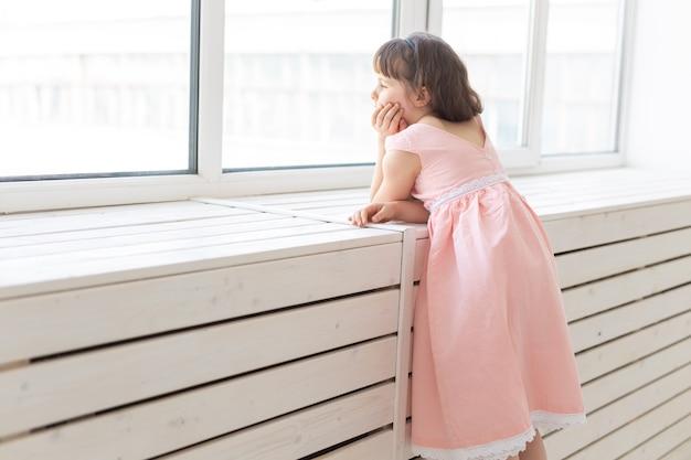 Dromerig meisje in een roze jurk kijkt uit het raam