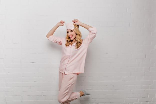Dromerig meisje in grijze sokken dansen met tong uit in de ochtend. romantische jonge vrouw in katoenen pyjama's en roze eyemask die pret hebben.