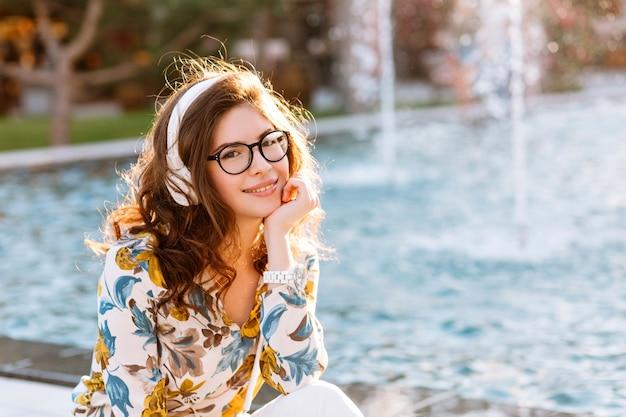Dromerig meisje in wit polshorloge en glazen, zittend op een prachtige fontein die gezicht met de hand ondersteunt