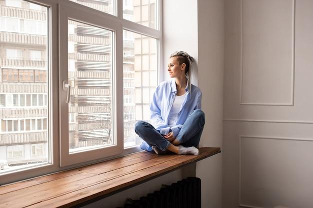 Dromerig meisje met dreadlocks zittend op een raam