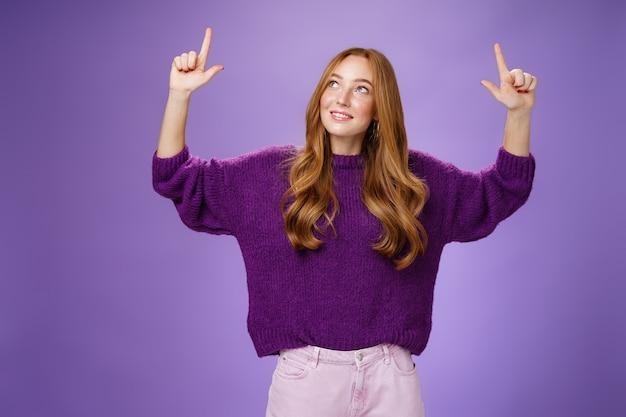 Dromerig meisje met rood haar en sproeten in een warme, gezellige paarse trui die de handen opheft en omhoog kijkt met een geïntrigeerde en blije gecharmeerde uitdrukking die lacht als een nieuwsgierig product over de violette muur.