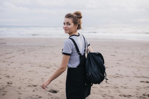 Dromerig meisje met zwarte rugzak die over de schouder kijkt tijdens een wandeling langs de kust. buiten foto van vrolijk wit vrouwelijk model tijd doorbrengen op het strand.