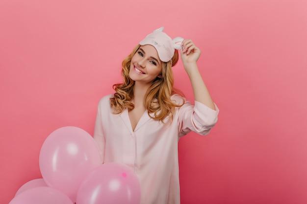 Dromerig meisje raakt haar oogmasker aan met een glimlach terwijl ze op roze muur poseren. lachende geweldige vrouw in pyjama, met feestballonnen.