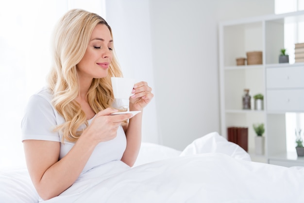 Dromerig meisje zit bed geniet van warme koffiegeur aroma