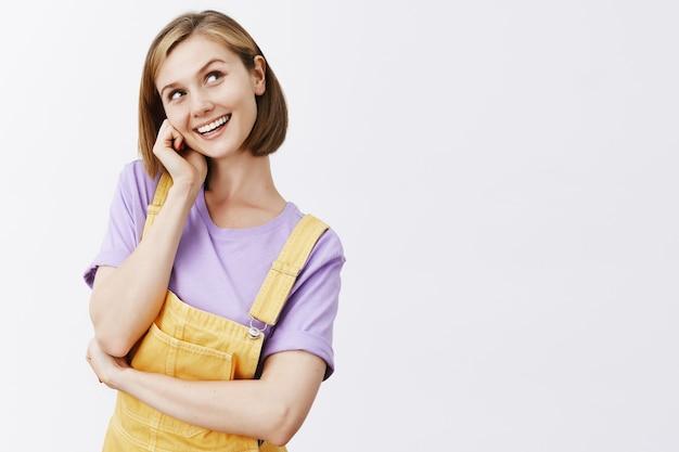 Dromerig mooi blond meisje, glimlachend en nieuwsgierig kijkend rechtsboven