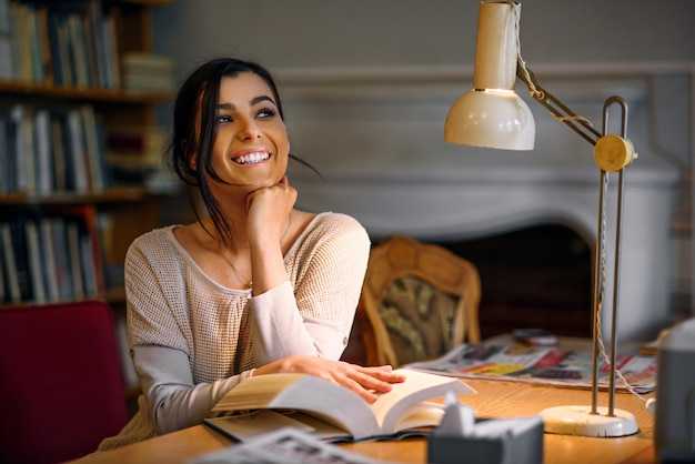 Dromerig mooi en enthousiast studentenmeisje met het perfecte boek van de glimlachlezing in universitaire bibliotheek onder een schemerlamp