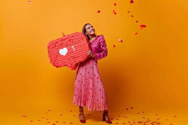 Dromerig romantisch meisje in een goed humeur tijdens fotoshoot met grote like in haar handen. model in modieuze blouse met franje