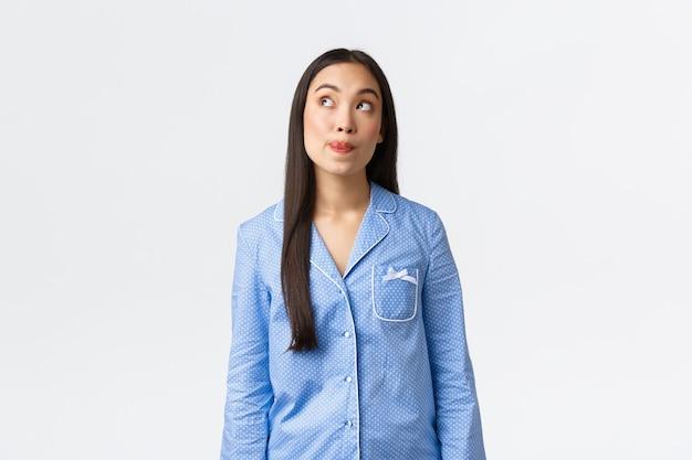 Dromerig schattig aziatisch meisje in blauwe pyjama verleidelijk om 's nachts iets lekkers te eten, lippen te likken van verlangen, linksboven attent te kijken, iets lekkers te denken of in beeld te brengen, witte achtergrond