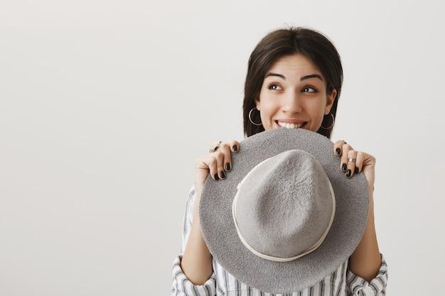 Dromerig schattig meisje kijkt naar links met verleiding en bijtende hoed opgewonden, vreugdevol glimlachend