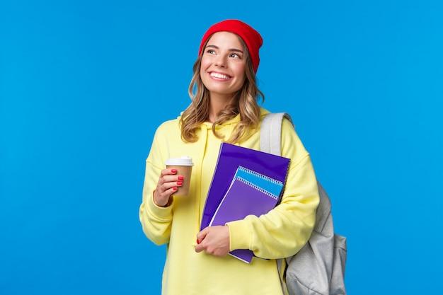 Dromerig schattig universiteitsmeisje dat zonnige lentedag overweegt op weg naar lessen, koffie en notitieboekjes vasthoudt, glimlachend opkijkt, rugzak draagt, staand