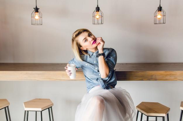 Dromerig stijlvol meisje met blond haar en roze lippen, zittend in een coffeeshop met houten stoelen en tafel. ze houdt een kopje koffie vast