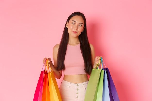 Dromerig trendy aziatisch meisje met boodschappentassen, kijkt nadenkend linksboven, besluit iets te kopen, zie goede verkooppromo, roze oppervlak.