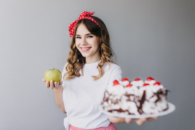 Dromerig wit meisje die grote verjaardagstaart met bessen houden en glimlachen. aantrekkelijk donkerharig vrouwelijk model kan niet beslissen wat ze moet kiezen tussen taart en appel.