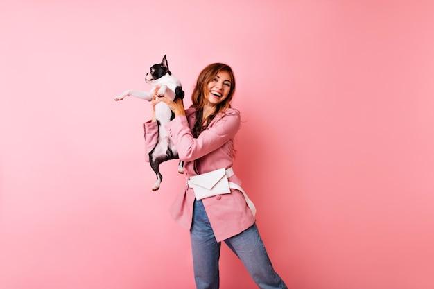 Dromerig wit meisje in casual kleding met franse bulldog. betoverende donkerharige dame speelt met haar huisdier en het uiten van positieve emoties.