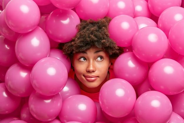 Dromerige, bedachtzame afro-amerikaanse vrouw geniet van feest, poseert tussen roze ballonnen, kijkt peinzend opzij en maakt plannen voor een feestje.