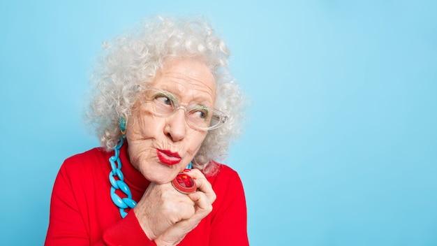 Dromerige, bedachtzame oudere europese vrouw houdt de lippen rond en kijkt opzij, denkt aan iets aangenaams gekleed in modieuze kleding