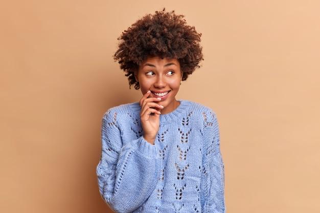 Dromerige bedachtzame vrouw met afro-haar kijkt weg glimlachend zachtjes geconcentreerd opzij grijnst positief gekleed in blauwe trui poses tegen bruine muur