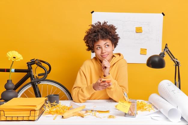 Dromerige blije afro-amerikaanse vrouw houdt moderne mobiele telefoon vast, bouwt blauwdrukken, werkt aan schetsen draagt sweatshirt heeft rotzooi op bureau